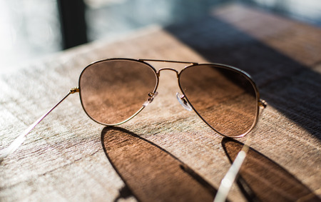 Aviator sunglasses on a wooden table closeup photo