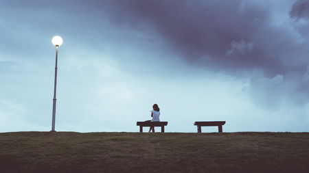 Woman sitting alone in a bench , vintage color