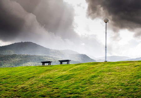 acceptation: wooden Bench on grass field , mountain background
