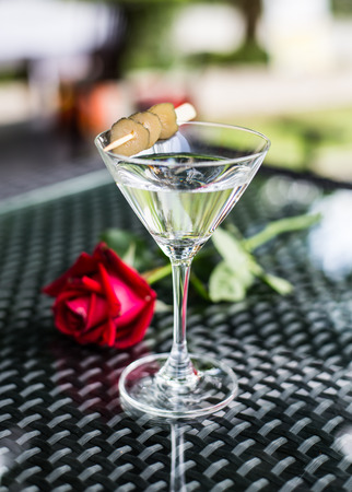drunks: alcohol glass with rose flower on glass table Stock Photo