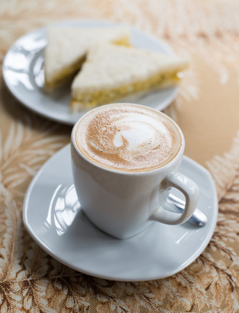 capuchino: cup of coffee and sandwich on glass table Stock Photo