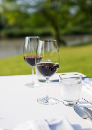 red wine on table set and green grass background in the\ garden