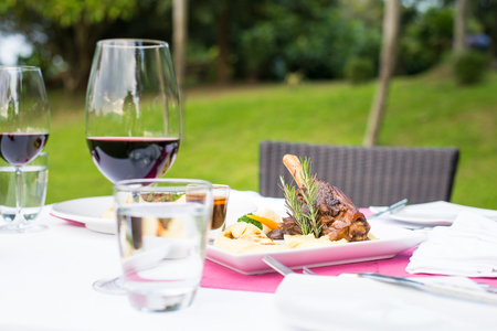 nude outdoors: lamb shank and red wine outdoor restaurant table setting