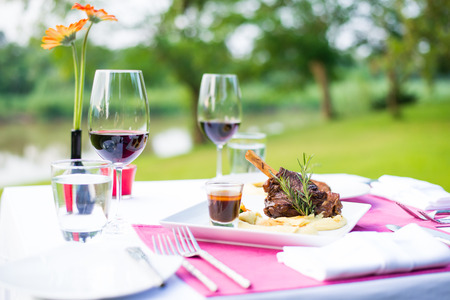 lamb shank and red wine outdoor restaurant table setting photo
