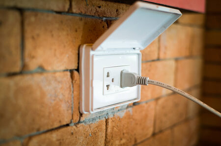 plugging: inserting an electrical plug into a wall socket