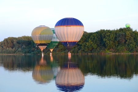 Beautiful colored aerostats flying over the river