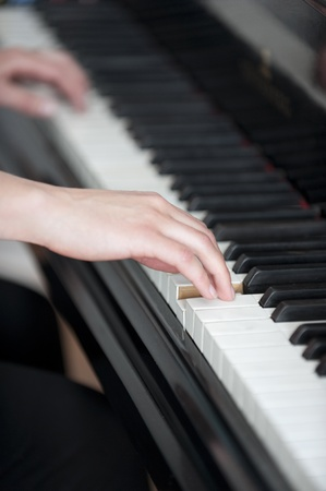 Young girls hands on piano keyboard photo