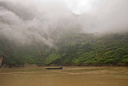 Barge on the Yangzte river in China with cloud shrouded mountains in background