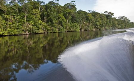 Water spray by fast moving boat on a tropical waterway Stock Photo