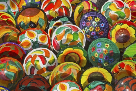 Assortment of hand-crafted, colorful Mexican ceramic plates with various patterns
