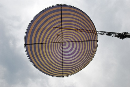 Spiral shaped disk suspended in sky from crane