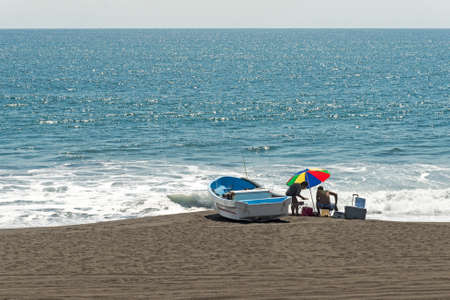 beached:  Beached boat with boaters by the Pacific Ocean, Guatemala Editorial