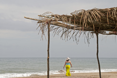 palapa: Woman on Pacific Ocean shore with palm leave sun shade in foreground Stock Photo