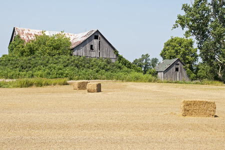 Old barn with hay bales in foreground, Prince Edward County, Ontario, Canada