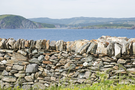 rock wall: Stone retaining wall with Atlantic Ocean in background, Newfoundland, Canada