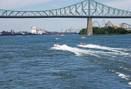 pleasure craft: Power boats speeding towards the Jacques Cartier bridge in Montreal, Quebec, Canada Stock Photo