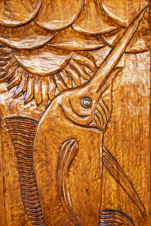 Wood bas relief carving of a fish with glossy finish