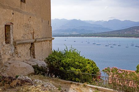 Corsican coastline with old house wall in foreground
