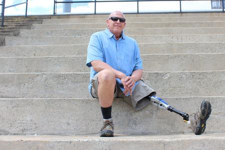 seated man: hombre sentado con la pierna extendida protésica