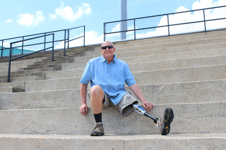 amputation: Man with prosthetic leg seated on concrete bleachers