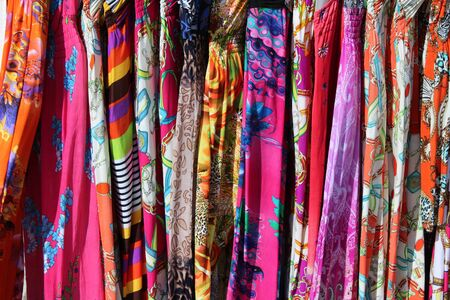 Rack of colorful dresses at an outdoor flea market Stock Photo