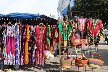 Colorful African dashikis, dresses and woven bags at an outdoor flea market Stock Photo