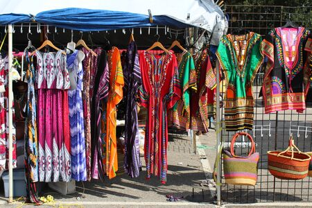 Colorful African dashikis, sses and woven bags at an outdoor flea market