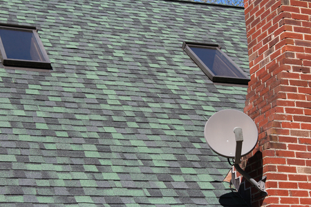 Satellite dish on green roof with skylights Stock Photo