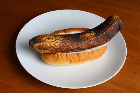 Rotten banana in a bun with mayonnaise