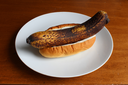 Unpeeled banana in a bun with mayonnaise