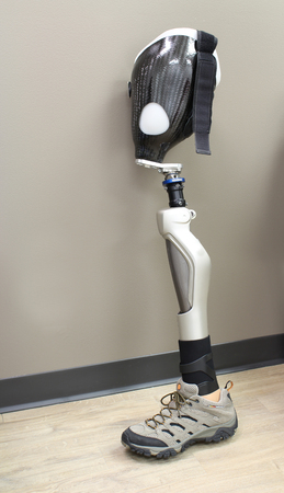 Leg prosthesis with shoe, leaning against a wall