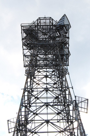 View looking up at a tall communications cell antenna tower against a light sky