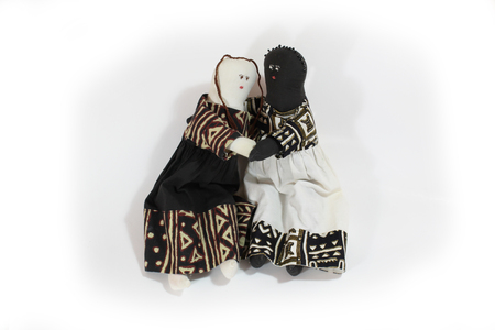 Black doll and white doll embrace concept forgiveness, reconciliation