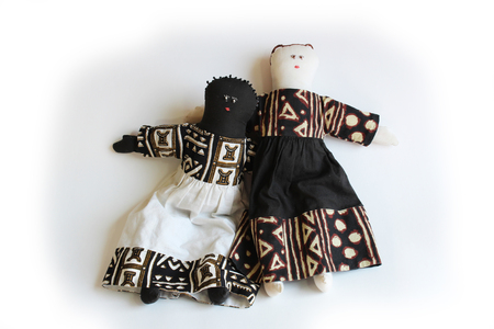 White doll with arm over shoulder of black doll concept inclusion