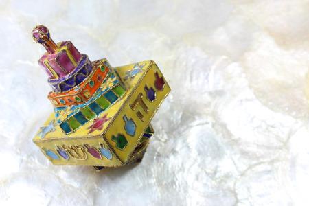 Colorful cloisonne Hanukkah dreidel on soft white background, space for text