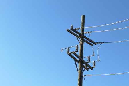 Terminal end of power pole against a deep blue sky Stock Photo