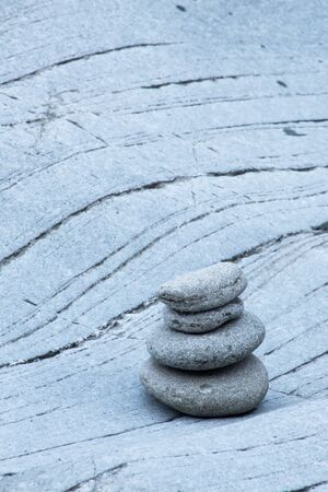 Four grey stacked stones on wavy rocks, space for text
