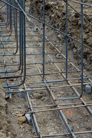Construction site view of supported grid of steel rebar reinforcement, vertical aspect