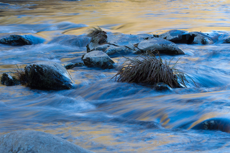 Blue and gold rocks abstract with water reflections of the sky and autumn leaves, horizontal aspect Stock Photo