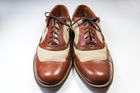 Front view of a pair of mens vintage leather and webbing shoes on white, horizontal aspect Stock Photo