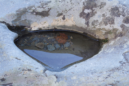 Puddle in a rock with pebbles and a leaf submerged, horizontal aspect Stock Photo