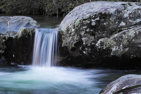 Small waterfall cascade between two large rocks, horizontal aspect Stock Photo