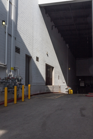 Loading dock outside a white block building with inclined street, vertical aspect Stock Photo