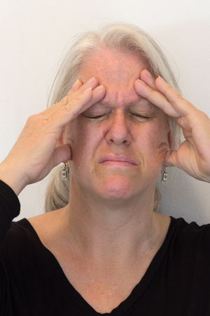 Mature woman with fingers to forehead, headache pain, eyes closed, neutral background, vertical aspect