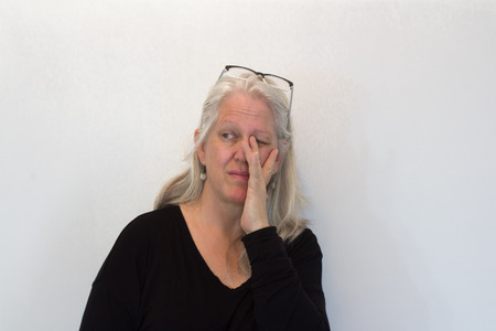 Mature woman with long white hair, hand rubbing eye, glasses raised, neutral background, copy space, horizontal aspect