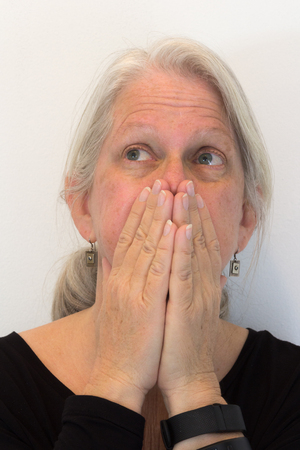 Mature woman with hands over mouth looking up and away, natural no makeup, neutral background, vertical aspect