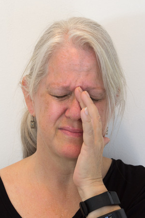 Mature woman, natural no makeup, sinus pressure, pain, hand to face, neutral background, vertical aspect
