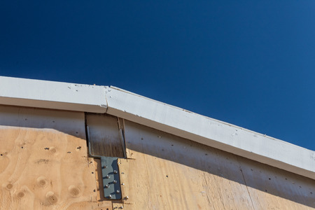 Residential construction detail with bracket for laminated ridge beam, plywood sheathing, copy space, horizontal aspect
