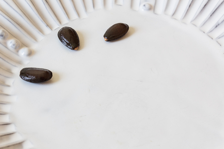 White fluted plate with three large, black cherimoya seeds, Annona cherimola, copy space, horizontal aspect