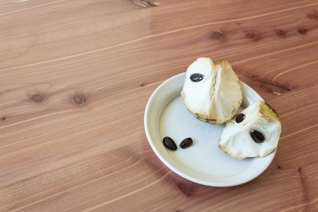 Aligned right small dish with chunks of ripe cherimoya fruit Annona cherimola and black seeds, copy space on wood background, horizontal aspect